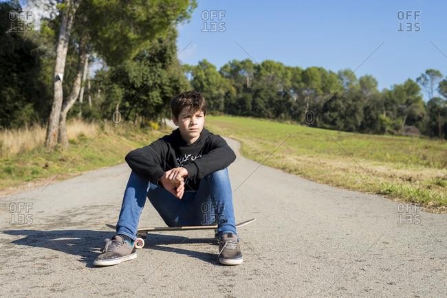 Handsome teen male with a skateboard sitting on asphalt road