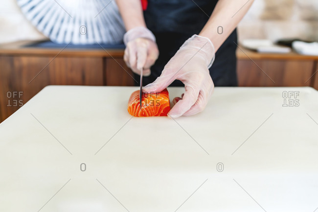 Japanese chef expert in sushi with his knife cutting salmon
