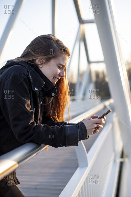 young adult woman laughing in a footbridge with her phone