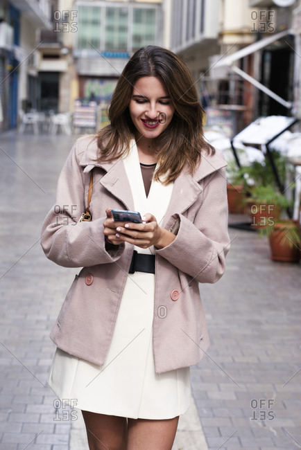 Smiling young woman handles her phone on the city streets