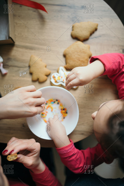 Mother and daughter have fun with cookies in the kitchen.