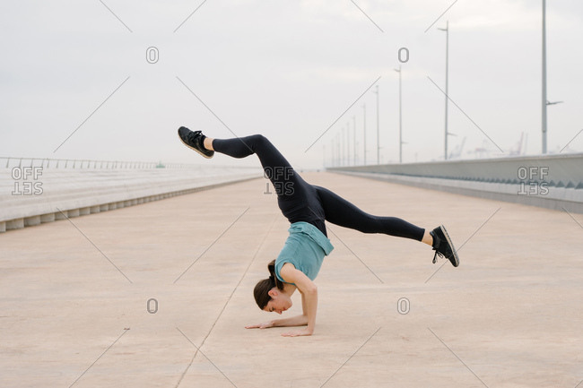 sporty girl doing a handstand while dancing in the street