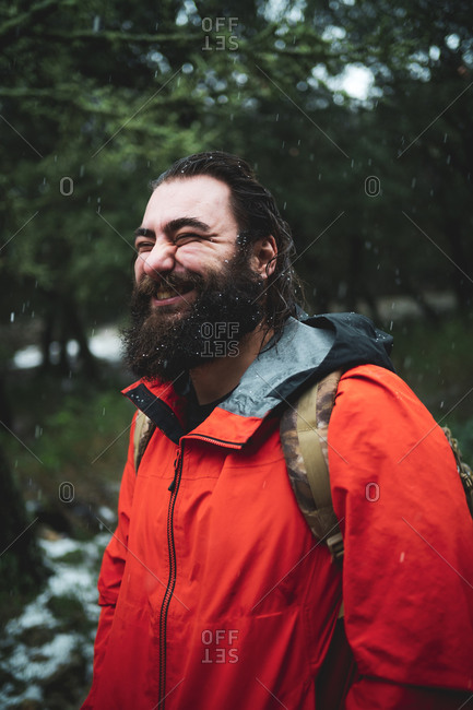 Bearded man in nature during a snowy day smiling happily