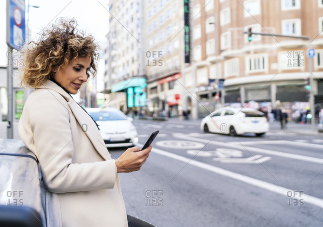 woman with hair calling for a taxi from her smartphone