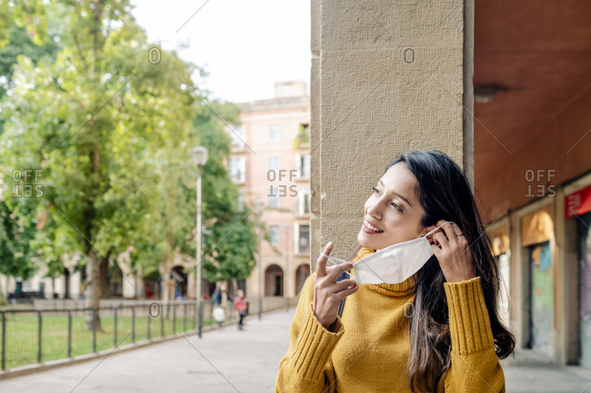 Smiling woman putting on a mask by square in Barcelona