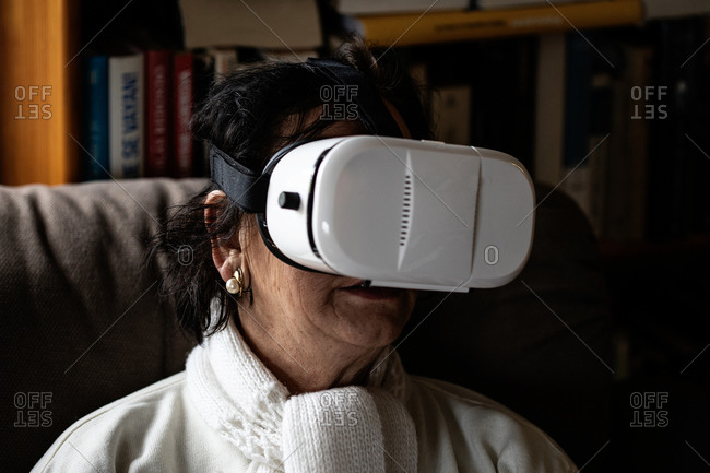 senior woman using the VR simulator on the living room