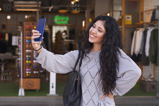 Pretty young woman makes a selfie on the city streets