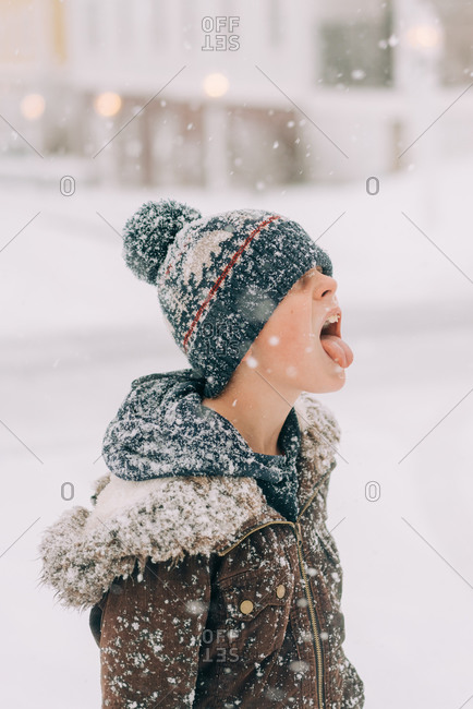 boy with woolly hat catching snow flake on his tongue