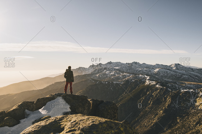 Young man admiring rugged snowcapped mountain landscape at sunset, Gredos, Spain