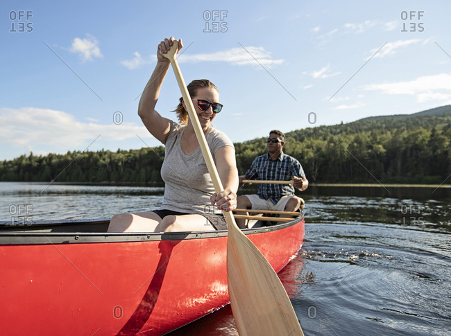 Woman smiles while paddling canoe on lake with african american friend