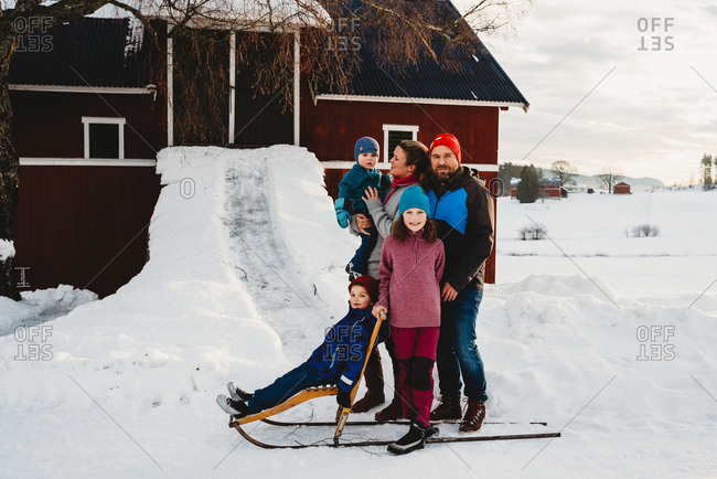 Beautiful family standing by red barn in Norwegian countryside in snow