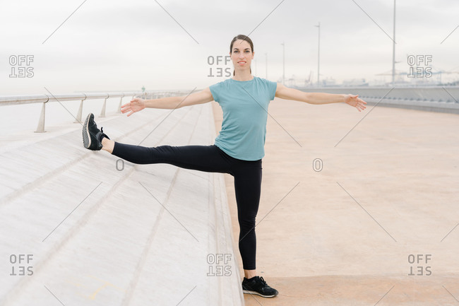 Girl practicing side stretch, open arms, yoga posture, on the street