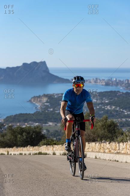 Cyclist climbing Cumbre del Sol hill with view of mediterranean sea.