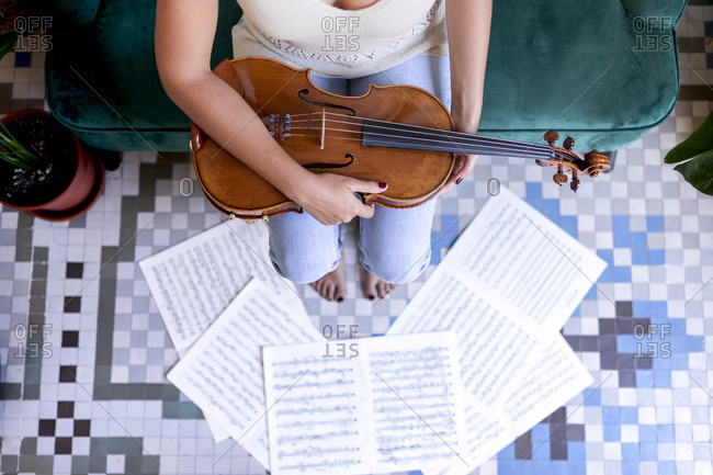 Sitting girl holding a viola, sheet music surrounding her bare feet.