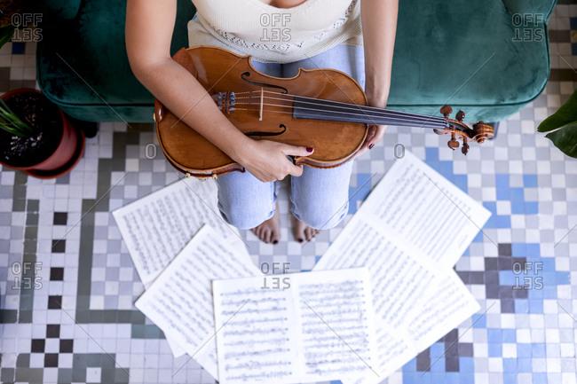Sitting girl holding a viola, sheet music surrounding her bare feet.