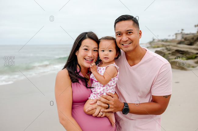 Glowing expectant Asian mom and proud dad holding daughter at beach