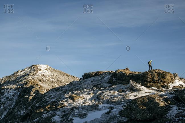 Lone hiker stands on peak in winter, Franconia Ridge, New Hampshire
