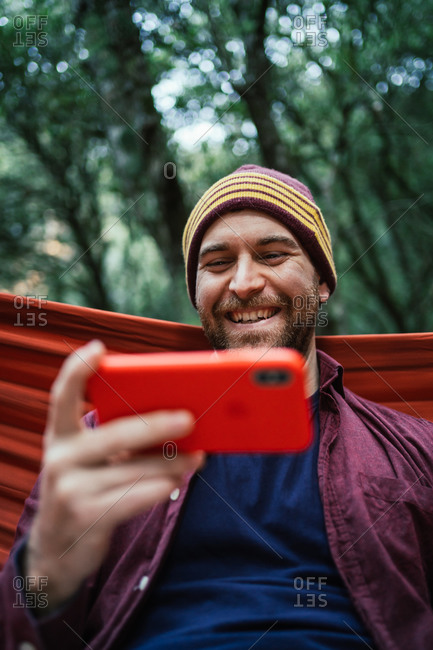 Man consumes content on his smartphone resting on hammock in woods