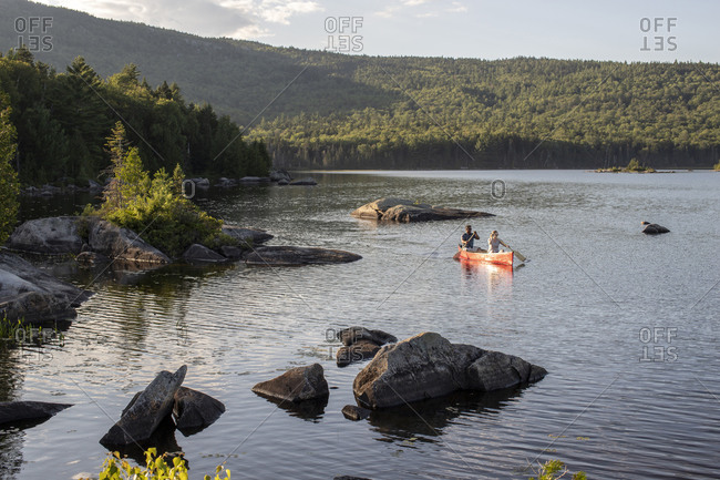 Couple paddles red canoe between rocks on wilderness lake in Maine