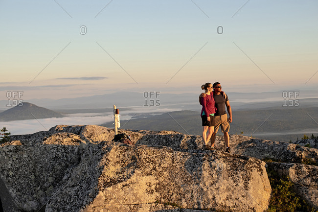 Couple embraces and hug after reaching summit of mountain in Maine