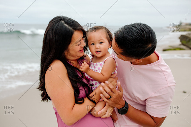 Asian husband and pregnant wife holding year old daughter at beach