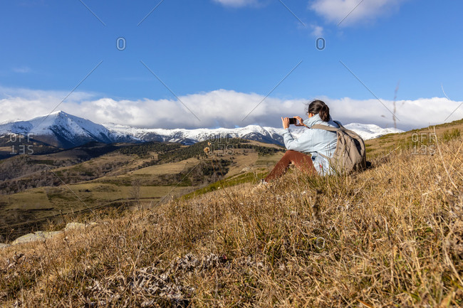 Spanish tourist woman sitting and take a picture with mobile phone