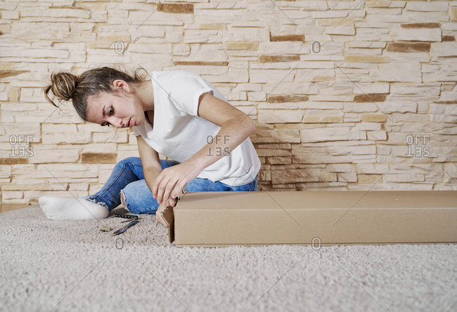 Front view of caucasian girl opening a brown paperboard box with