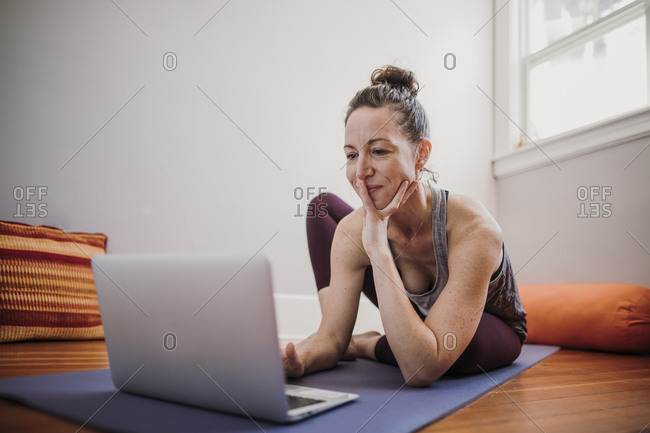 Woman prepares to practice yoga with laptop computer in her home