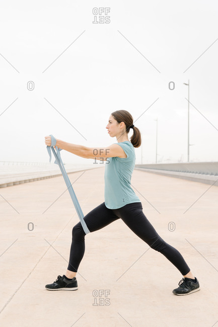Girl practicing yoga posture with elastic band arm on the street