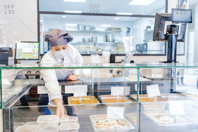 cook in her restaurant placing the portions in the display case