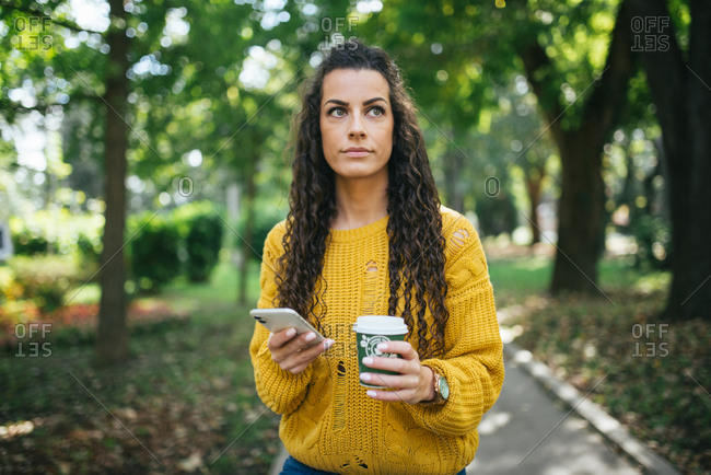 Woman holding smartphone and plastic cup of coffee in the park.