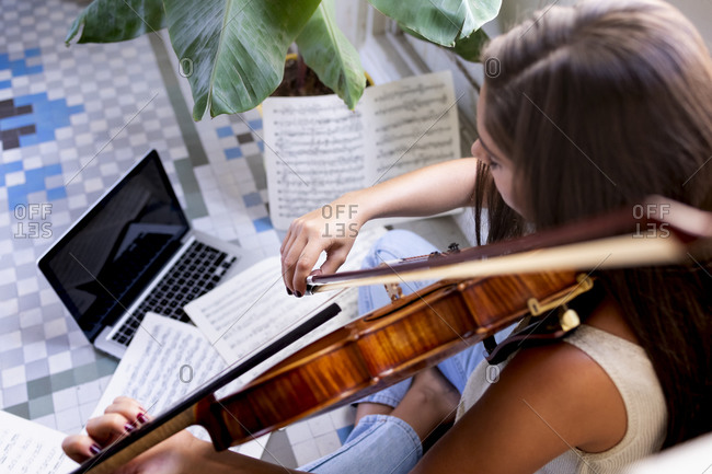 Girl musician plays viola with her laptop sitting on the floor.