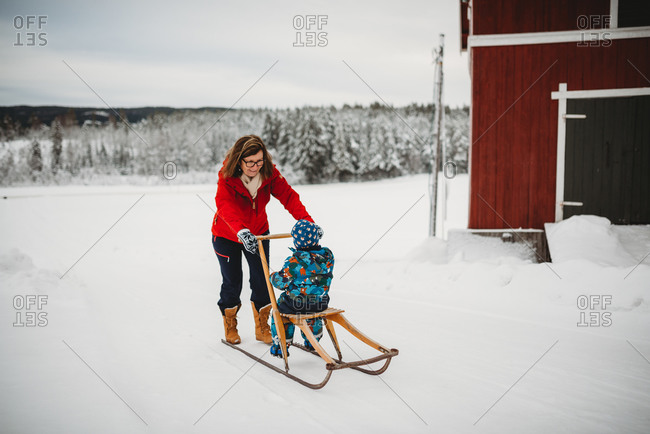 Grandma on old antique sleigh with grandchild in farm in Norway