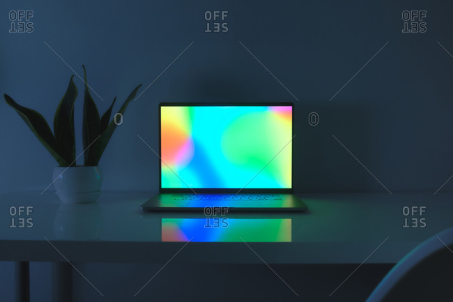 Laptop computer with vibrant screen standing on a table, low key