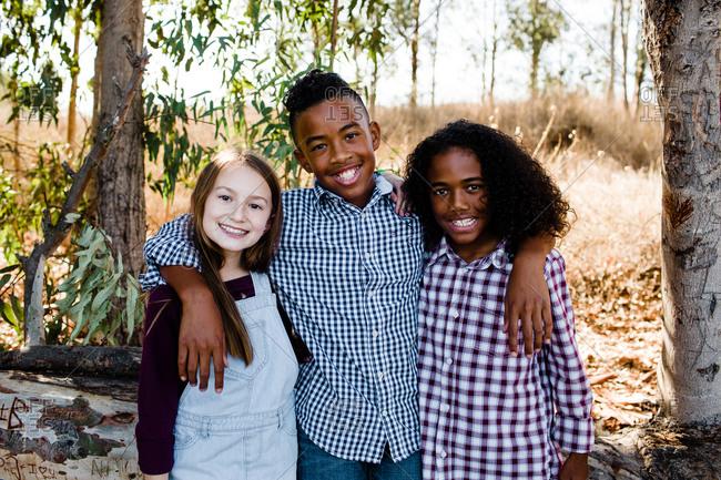Siblings Embracing & Smiling for Camera at Park in Chula Vista