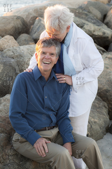Senior wife kissing husband at Cold Storage Beach on Cape Cod
