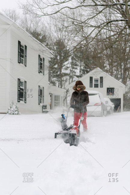 boy using the snow blower during a snowstorm in New England