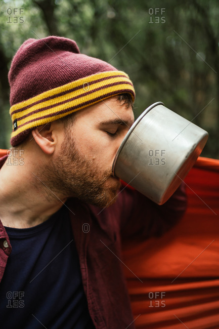 Man drinks hot beverage from a coffee pot in the forest