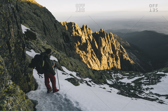 Young man assessing hike downhill situation during sunset at Gredos, Avila, Spain