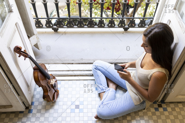 Musician woman texting on smartphone siting on the floor with a viola.