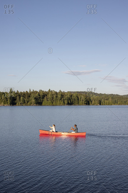 multi racial couple paddle red canoe on wilderness lake in Maine woods