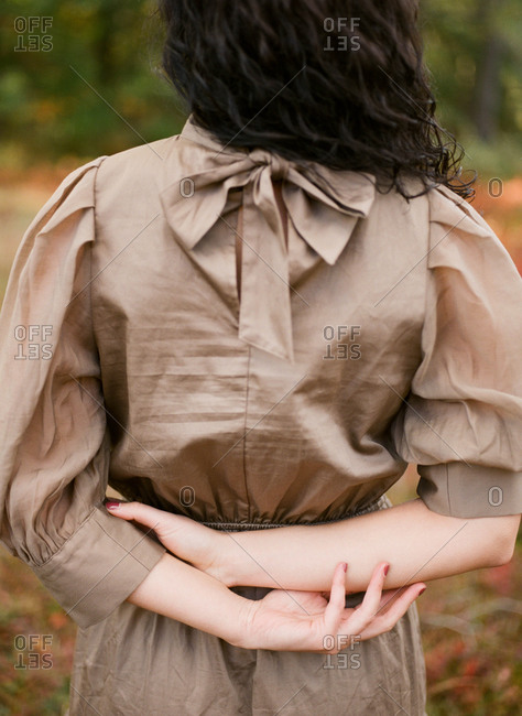 backside of woman with hands behind her back for fashion concept photo