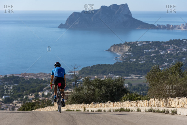 Cyclist going down Cumbre del Sol hill with view of mediterranean sea.