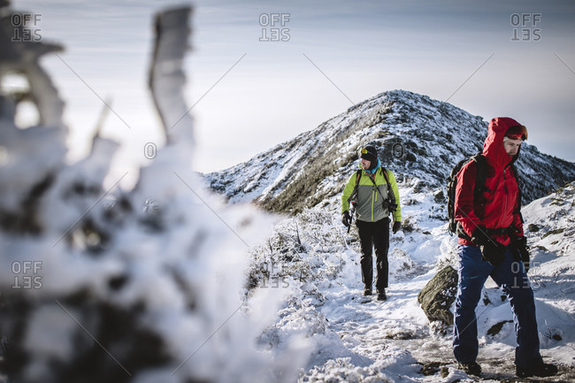 Two winter hikers on snowy frozen trail in mountains of New Hampshire