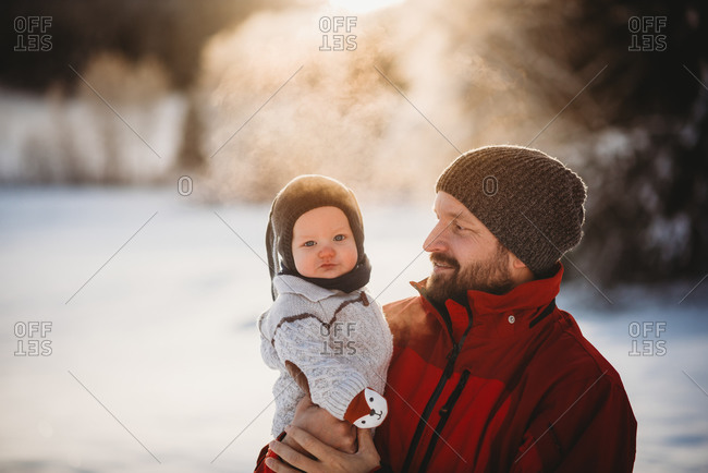 Dad and beautiful baby outside in snow in winter during golden sunset