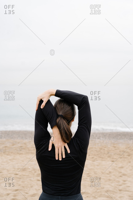 Young woman doing arm stretches as pre-exercise wain front of the sea