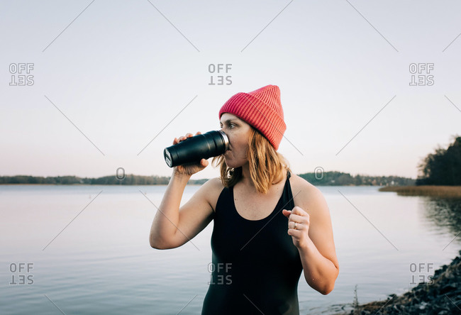 nordic woman drinking hot drink after cold water swimming in the sea
