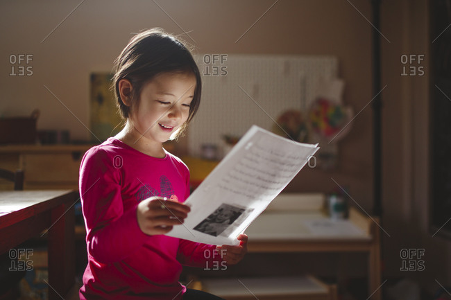 A smiling child in beautiful light studies a piece of paper, reading