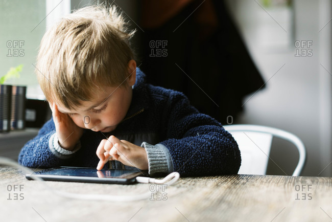 Little independent boy using his tablet for remote school at a table