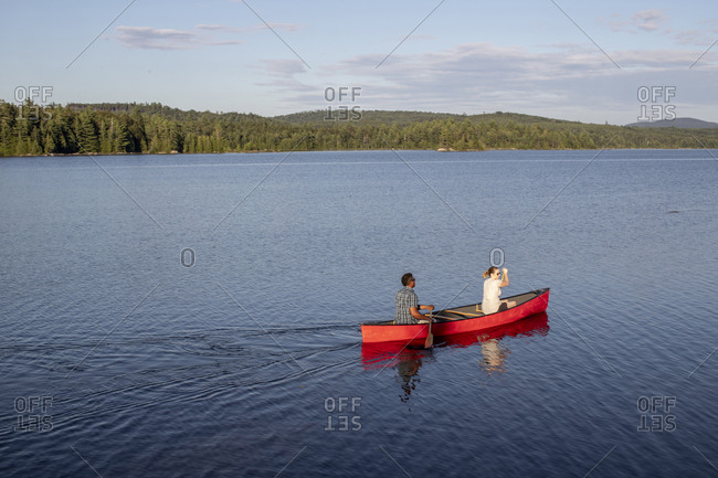 Elevated view of couple paddling red canoe on peaceful lake in Maine